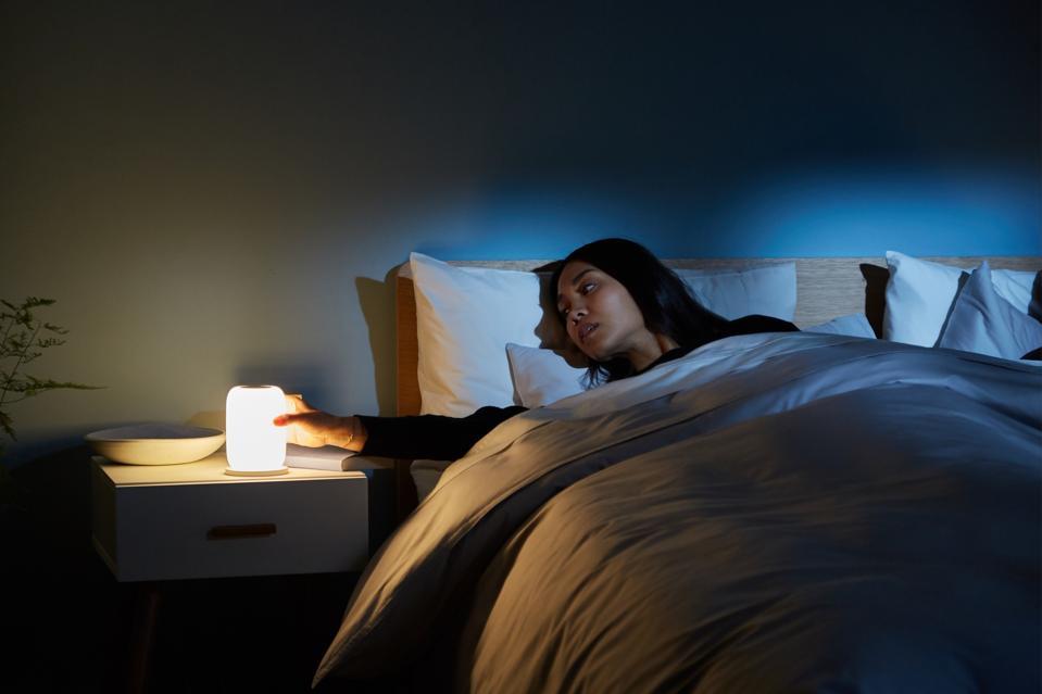 A woman in bed turns the Casper Glow Light in a dimly-lit bedroom.