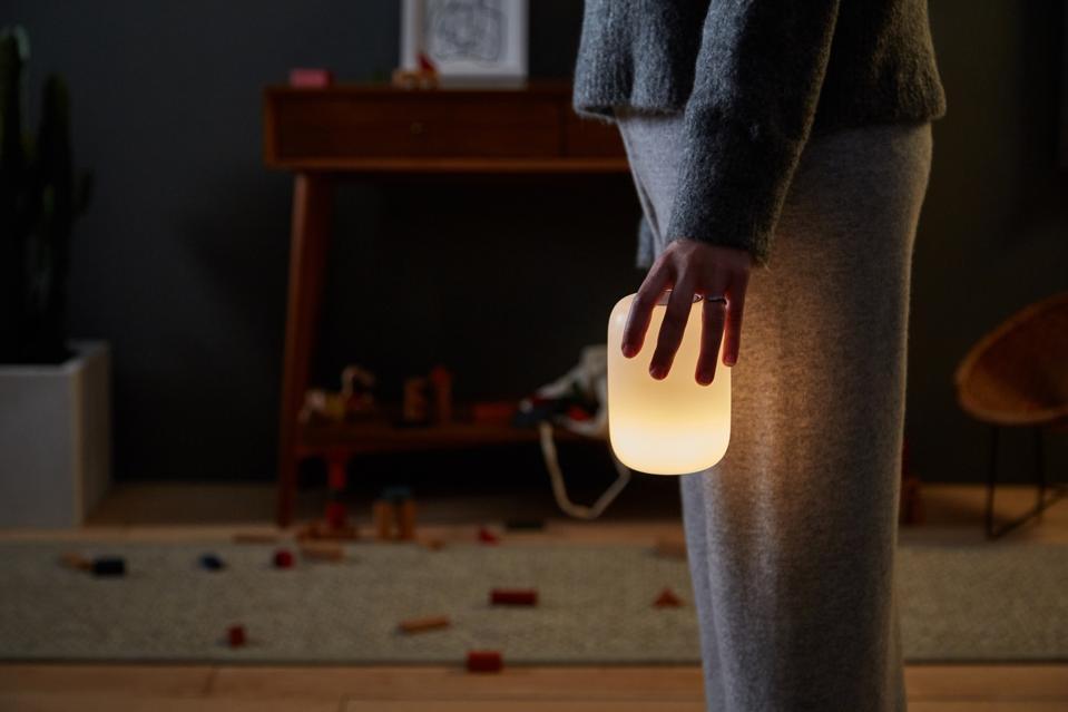 A woman in grey sleepwear holds a dim Casper Glow Light in a dark room.