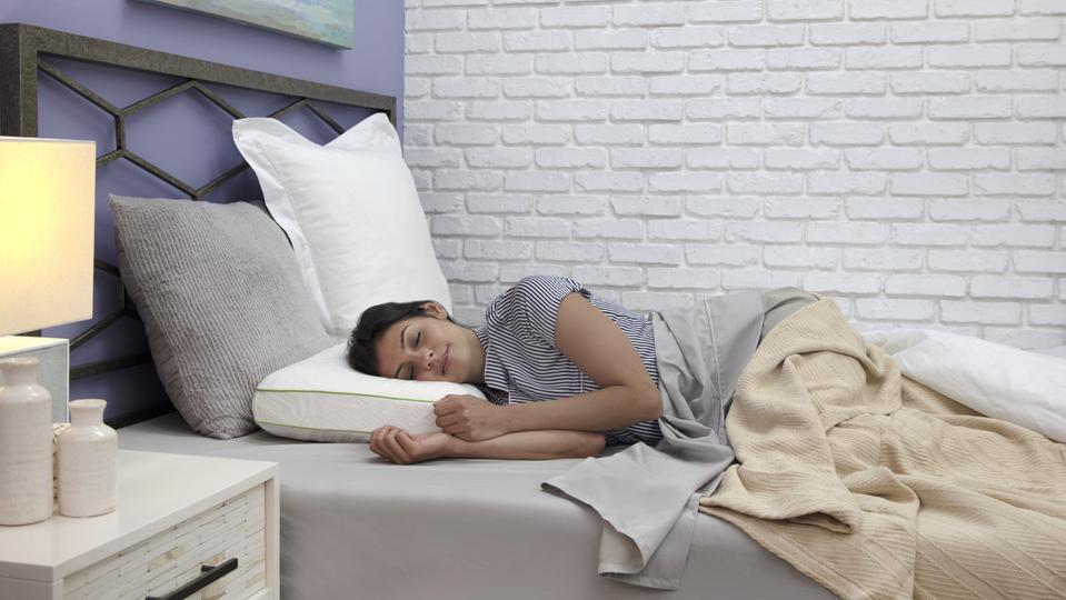A woman sleeps in bed with the Sensorpedic Memory Foam CBD Pillow.