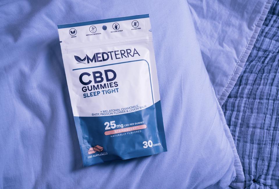 A package of Medterra Sleep Tight CBD Gummies on a purple blanket.