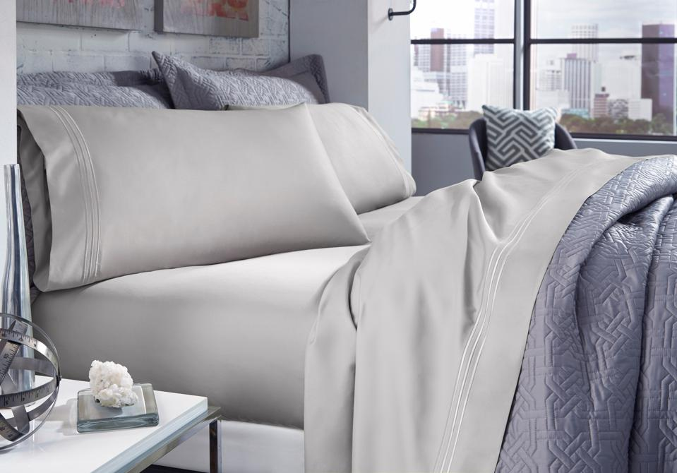 A bed outfitted in beige Purecare Recovery Sheet Set and a purple blanket.