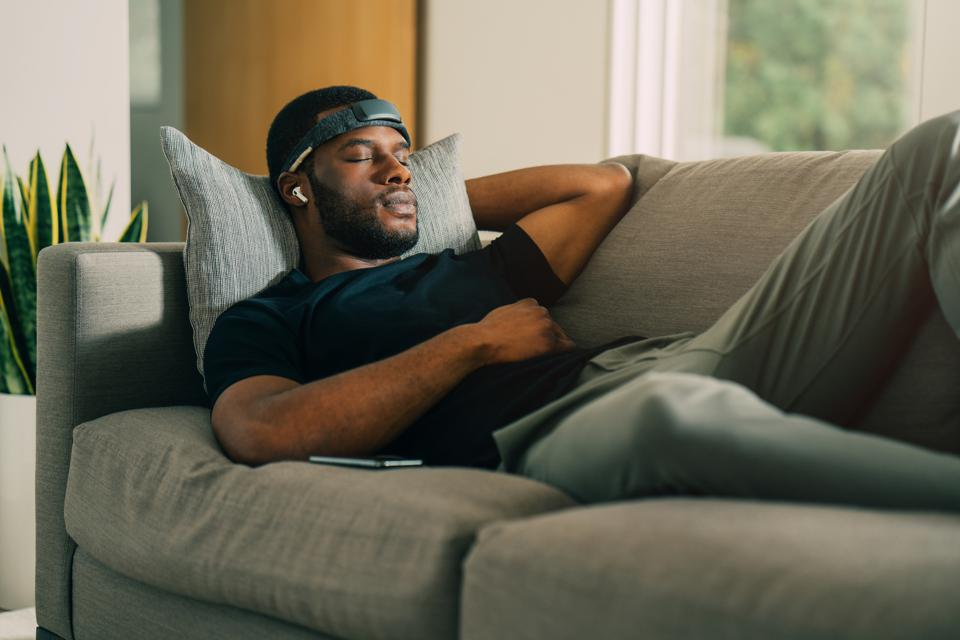A man sleeps on a couch with the Muse Headband