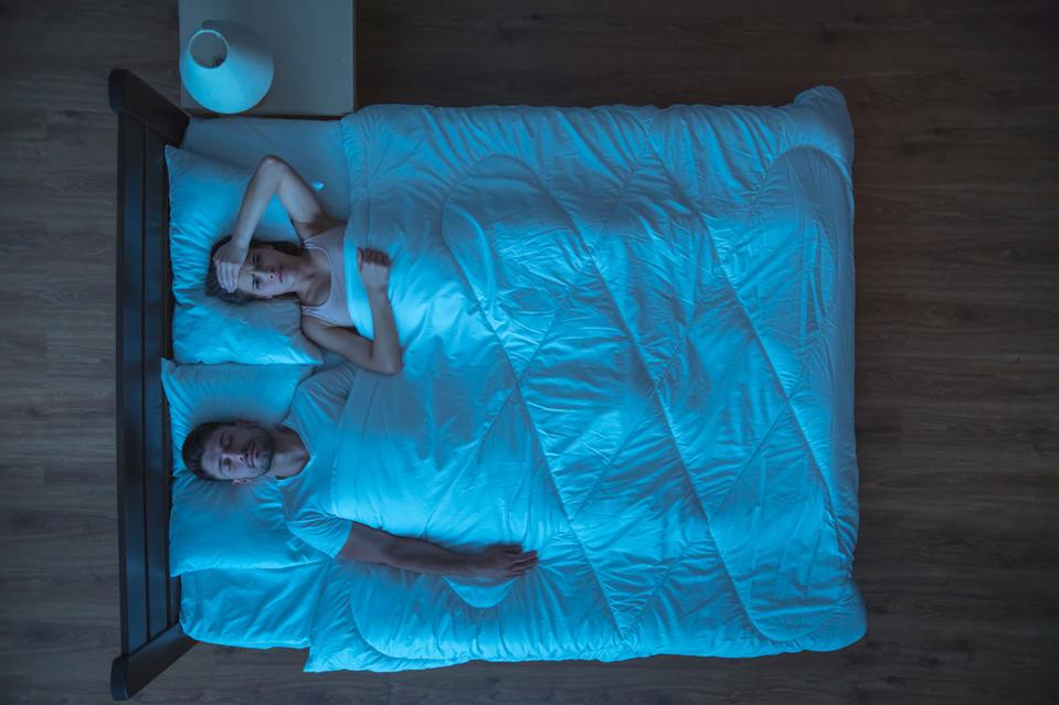 A woman lies in bed worried while the man next to her sleeps.