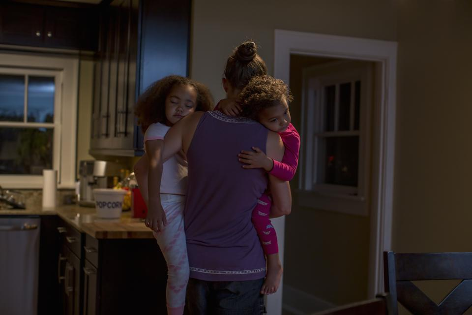 Mother carrying two sleeping daughters in a dimly lit kitchen.
