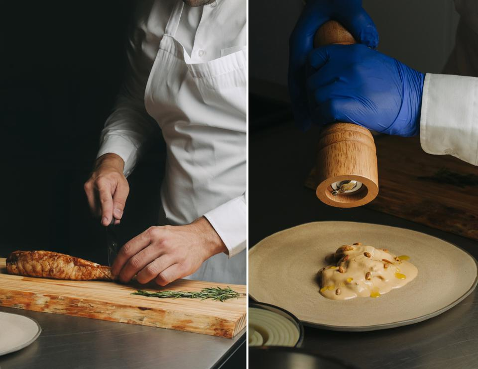 The hands of two chefs are seen at working preparing gourmet food for delivery