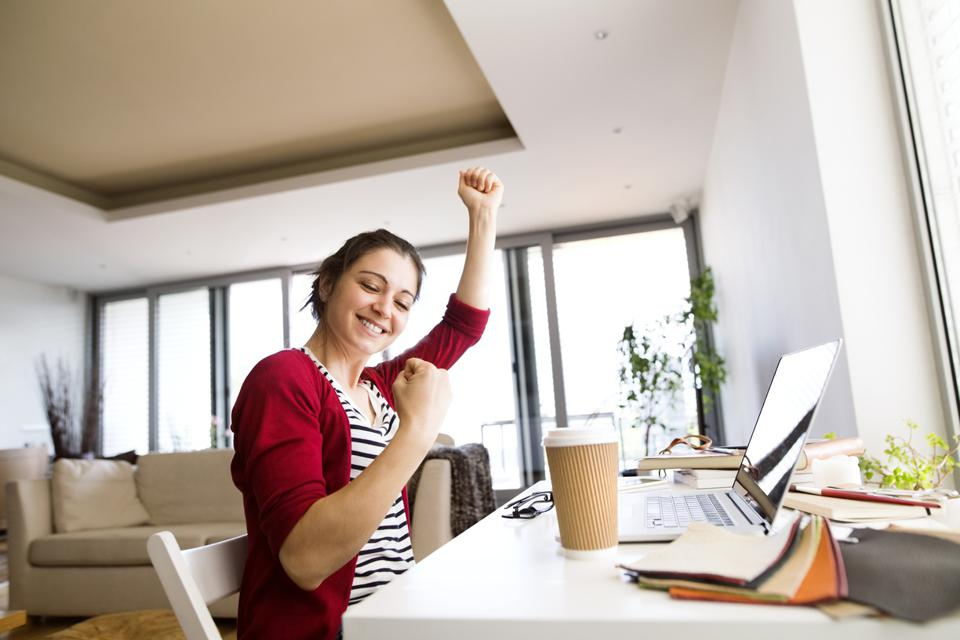 Happy woman at home receiving the good news of a job offer