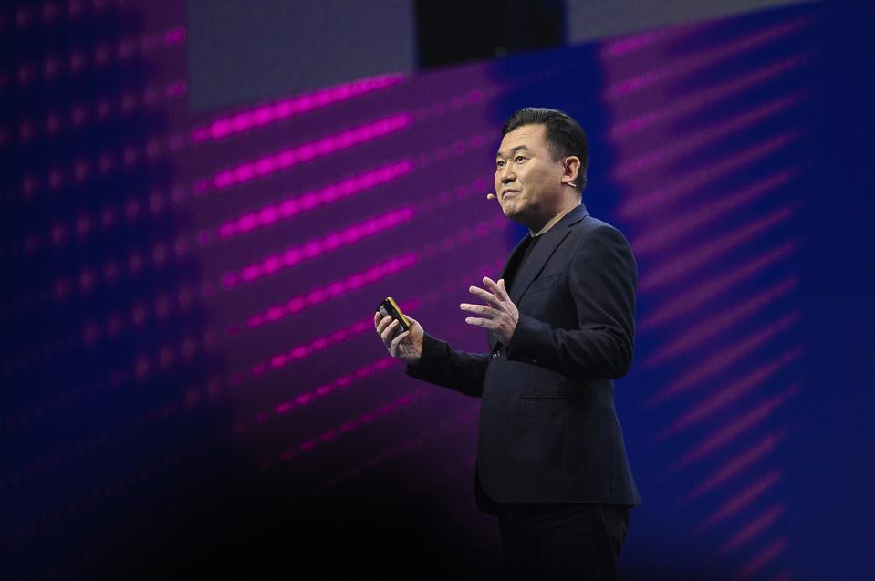 Rakuten CEO Hiroshi Mikitani, dressed smartly in black, addresses an audience.