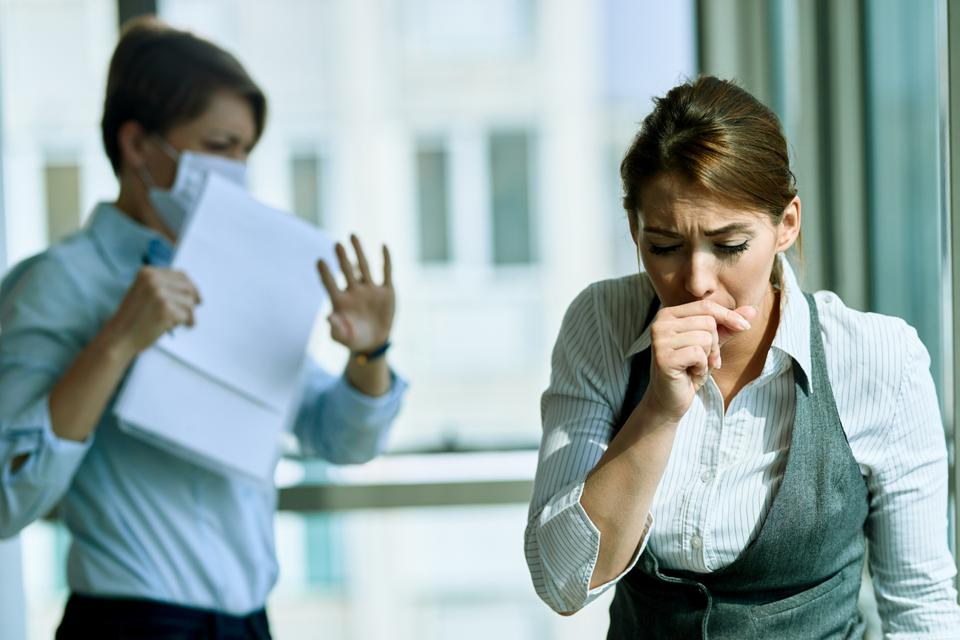 Young businesswoman coughing in the office.