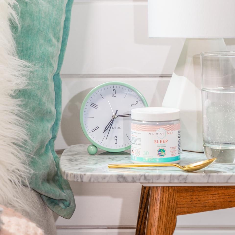 A jar of Alani sleep powder on a marble bedside table in front of an alarm.
