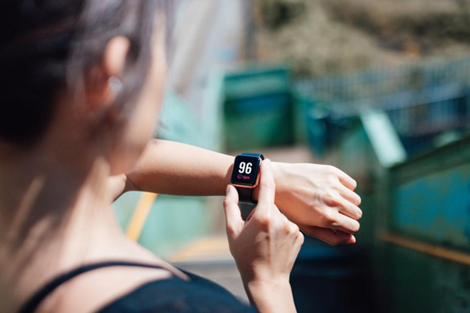 Young Woman Checking Heart Rate On Smart Watch