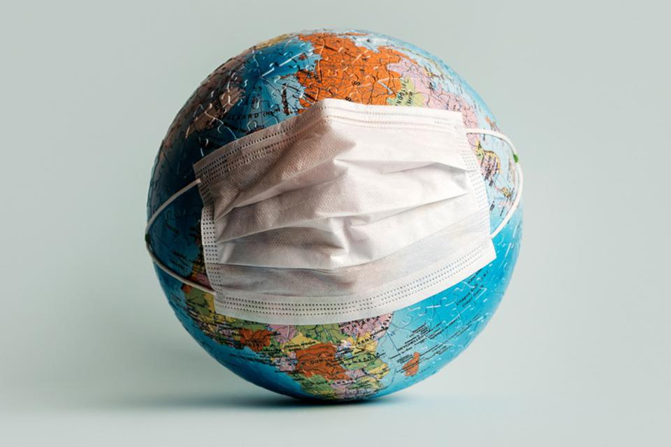 Globe made of jigsaw puzzles with a protective medical mask