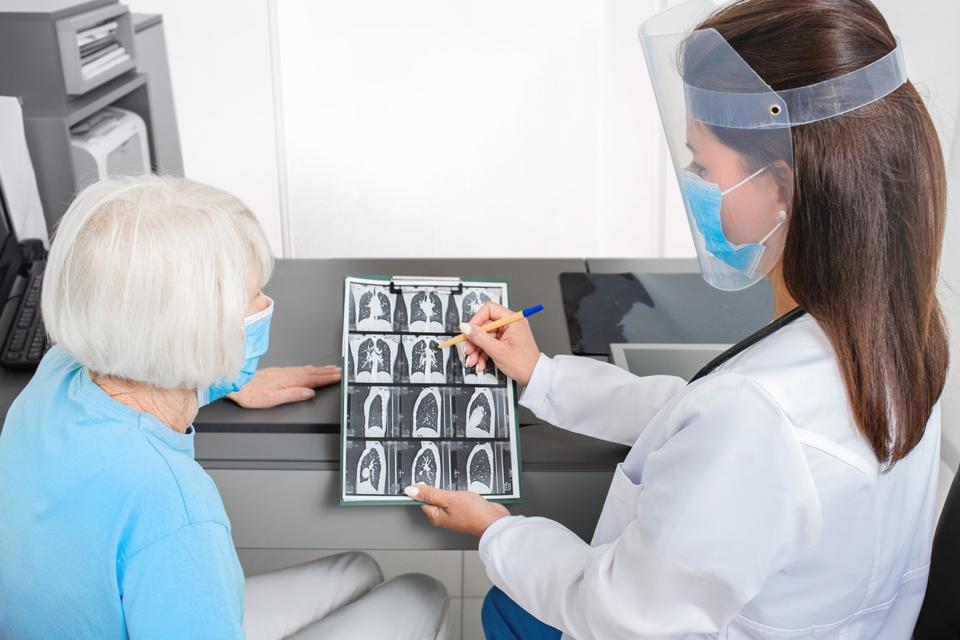 Pulmonologist showing an elderly patient a CT scan of her lungs. Pneumonia, coronavirus, lung disease