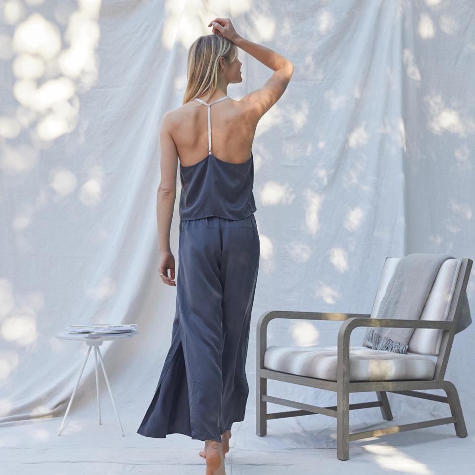 A woman models a navy blue Lunya Silk Cami Pant Set against a white backdrop.
