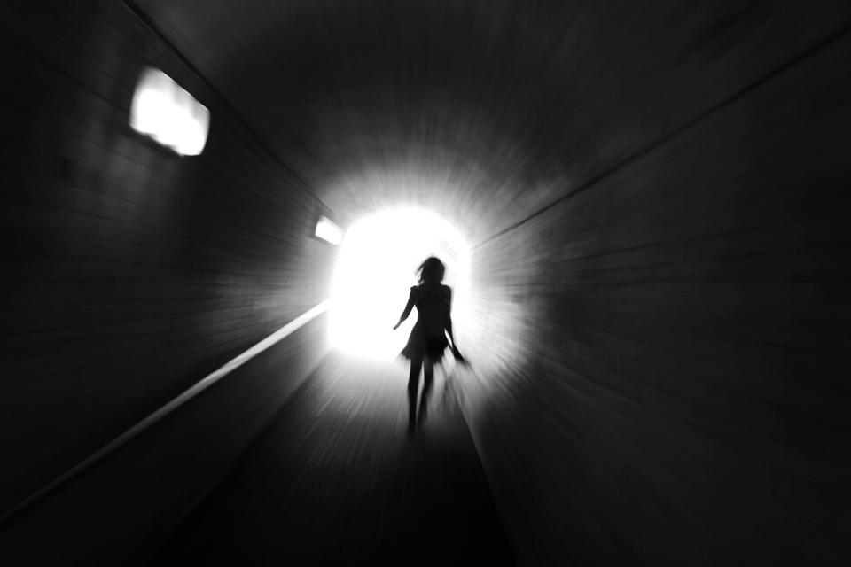 Rear view silhouette of woman walking towards light at the end of tunnel