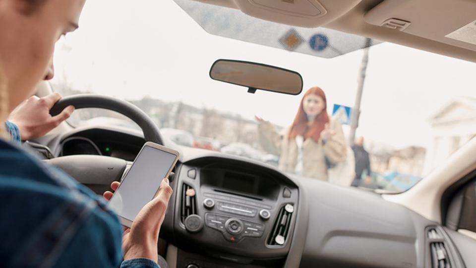 Distracted young male driver looking at the screen of his mobile phone while running over a pedestrian. Technology and transportation concept