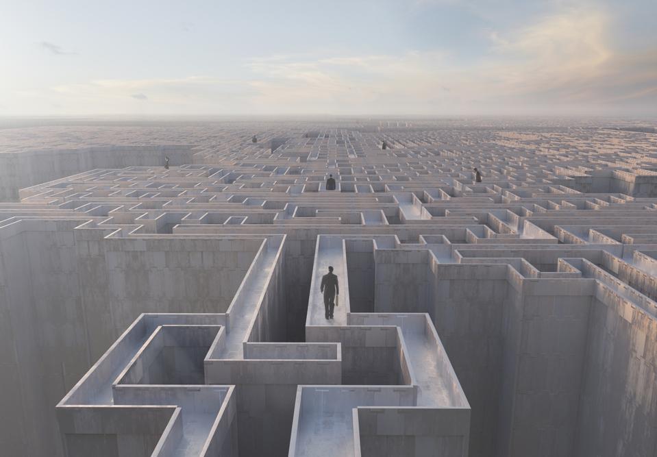 Businessmen walking on top of complex maze