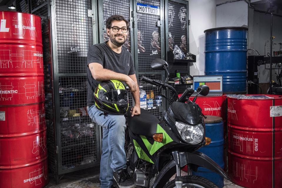 O homem branco de óculos e barba, vestindo uma camisa e jeans, está em pé perto de uma motocicleta usando um capacete.