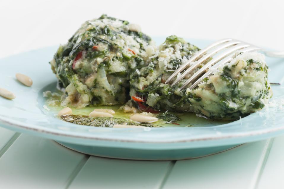 Two Italian strangolapreti spinach dumplings, a popular dish from Alto Adige.