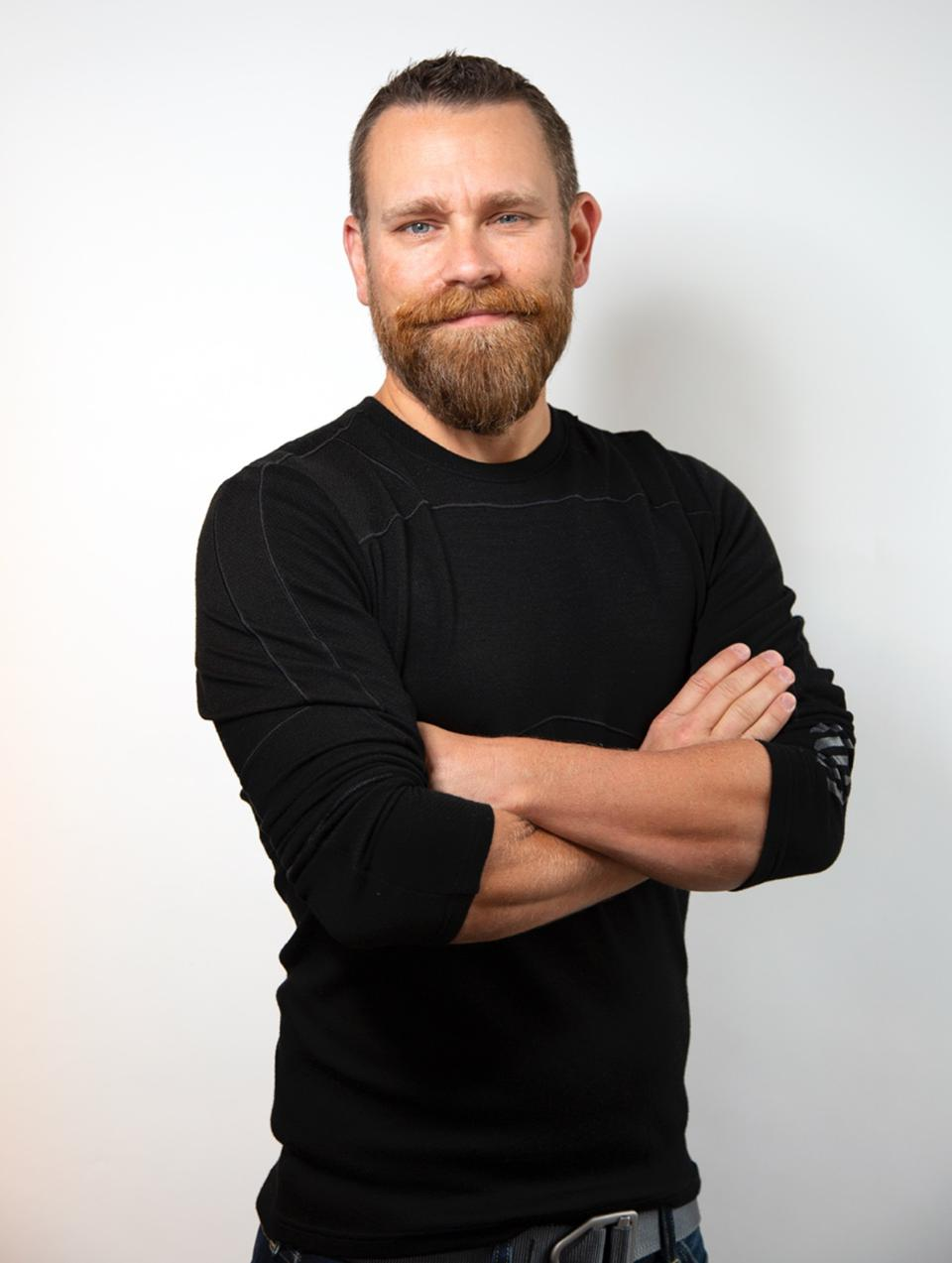 Headshot of Kristian Andersen in a black shirt in front of white wall.