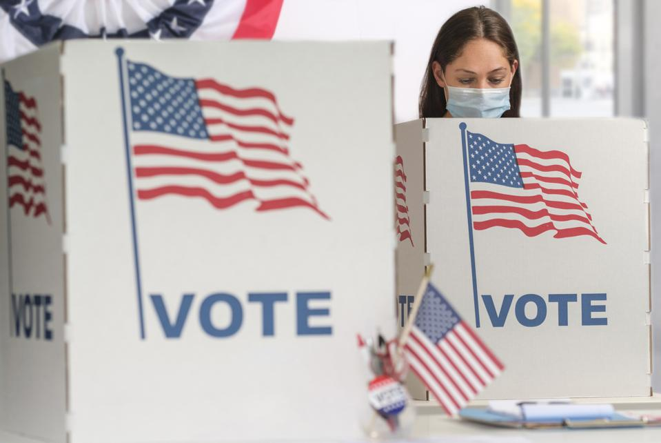 Woman in face mask voting