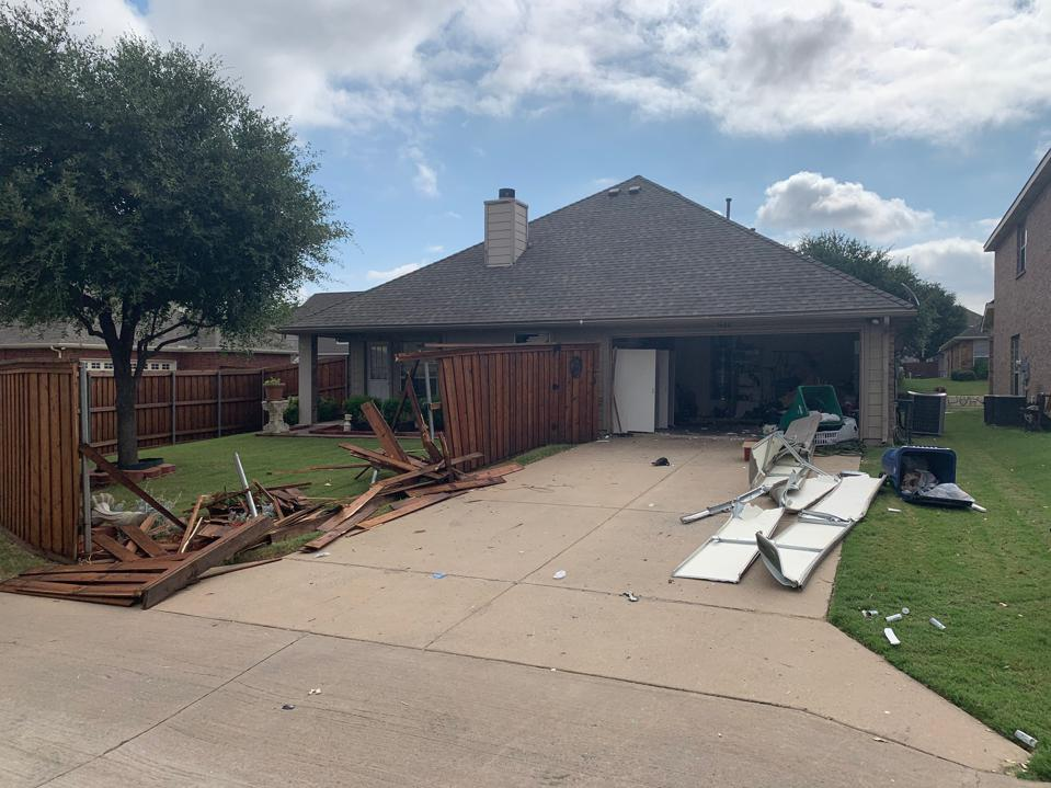 house with damaged fence and garage door