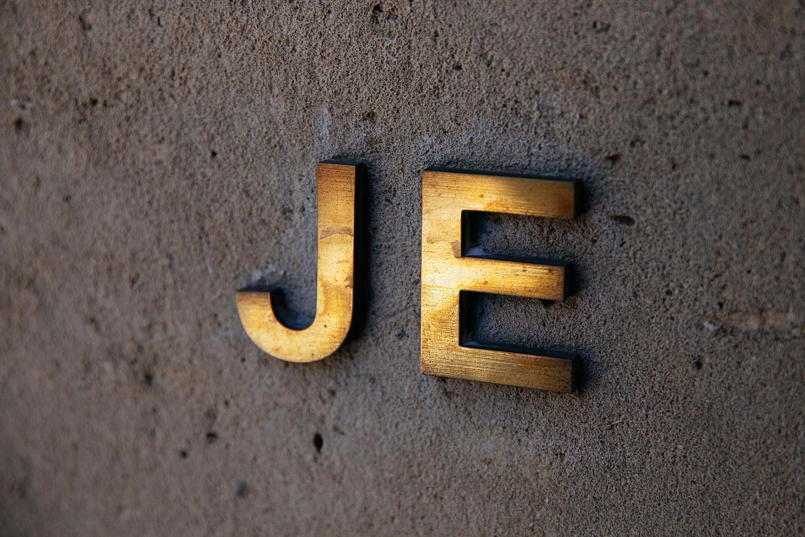 Brass initials J.E. on white concrete.