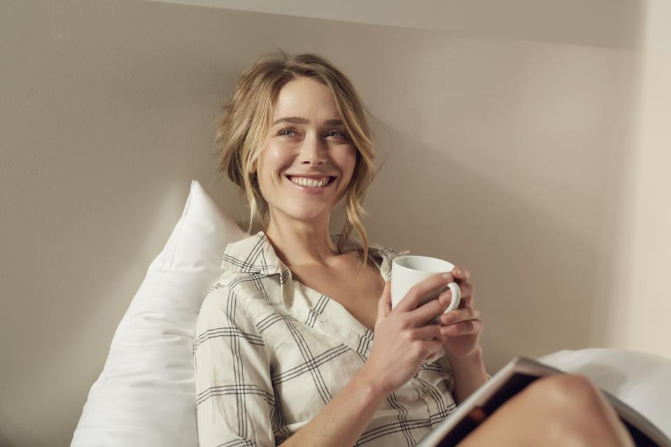 Portrait of happy woman sitting on bed with coffee mug and magazine