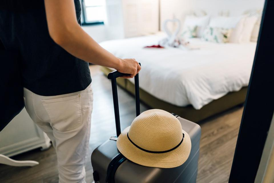 Close up of young Asian female traveller entering the hotel room at the hotel. She is carrying a suitcase with a straw hat and is on summer vacation