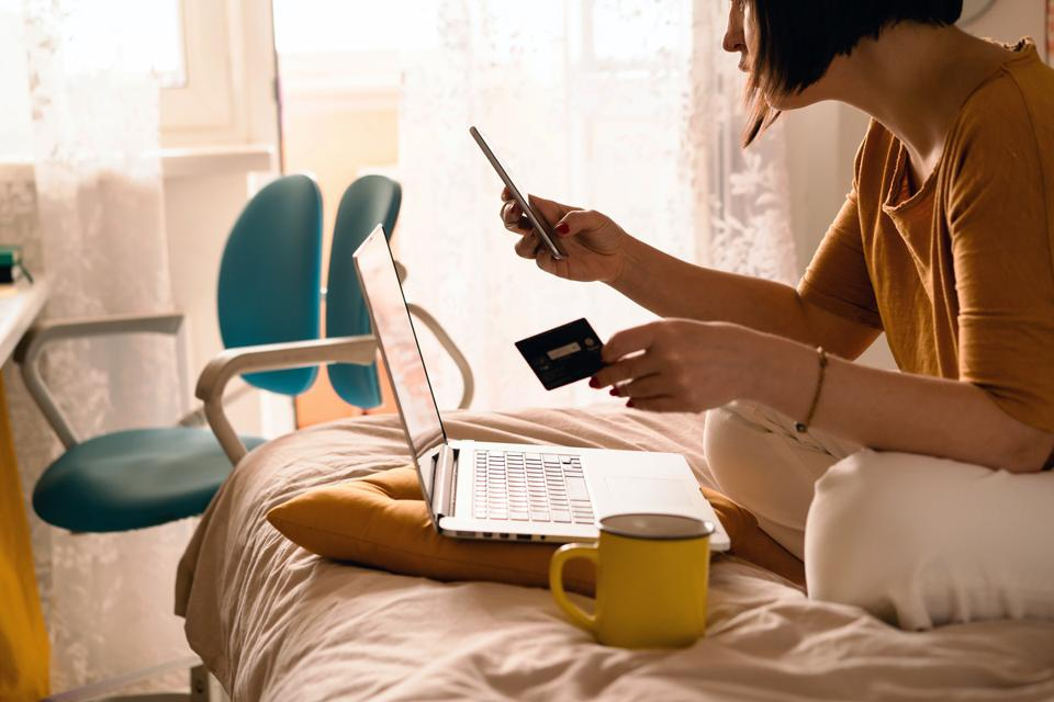 A woman in white jeans and a yellow sweater sitting on the bed in a yoga pose in front of a laptop and a cup of coffee