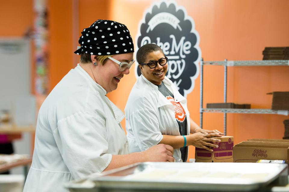 Two women in white lab coats boxing up baked goods in a commercial kitchen