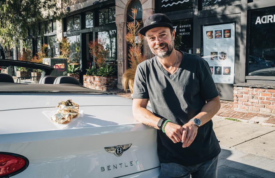 A delicious burger topped in caviar and gold leaf seats atop a Bentley in Venice, LA