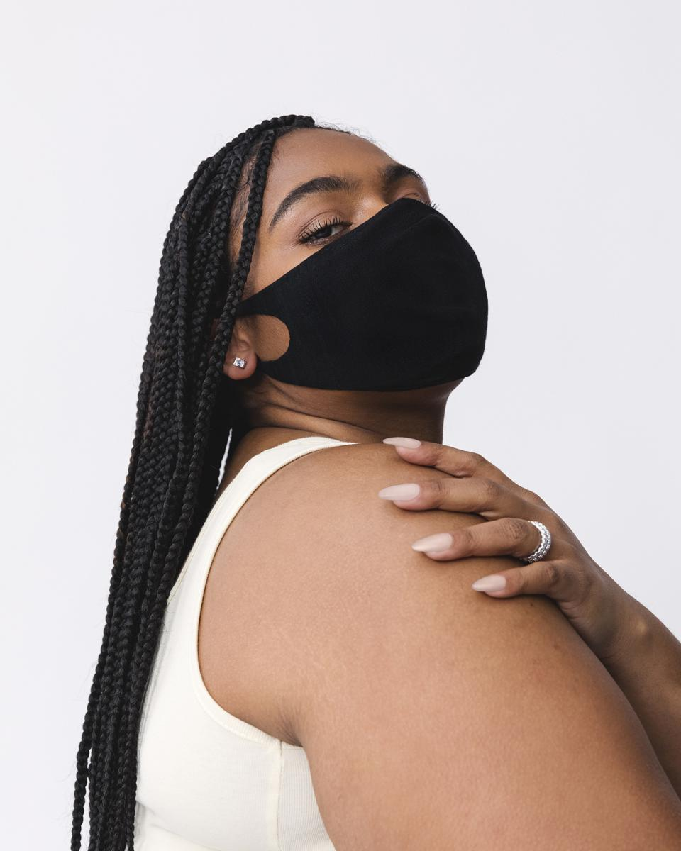 woman in black face mask and white top looks at camera