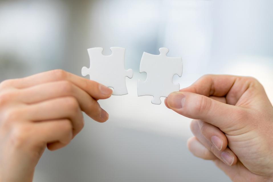 Mão masculina e feminina segurando quebra-cabeças, conceito de compatibilidade de negócios