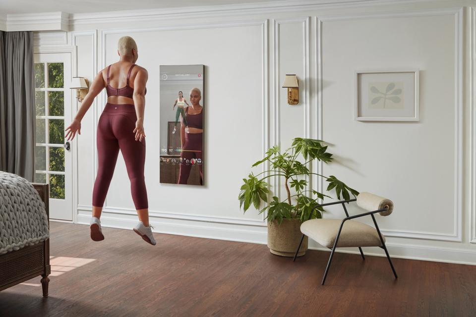 A woman does jump squats in front of the MIRROR at-home fitness system.
