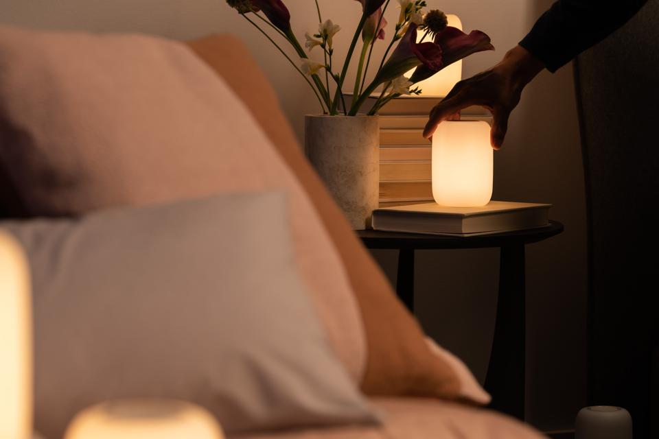 A hand twists the Casper Glow Light next to bed in a dimly lit room.