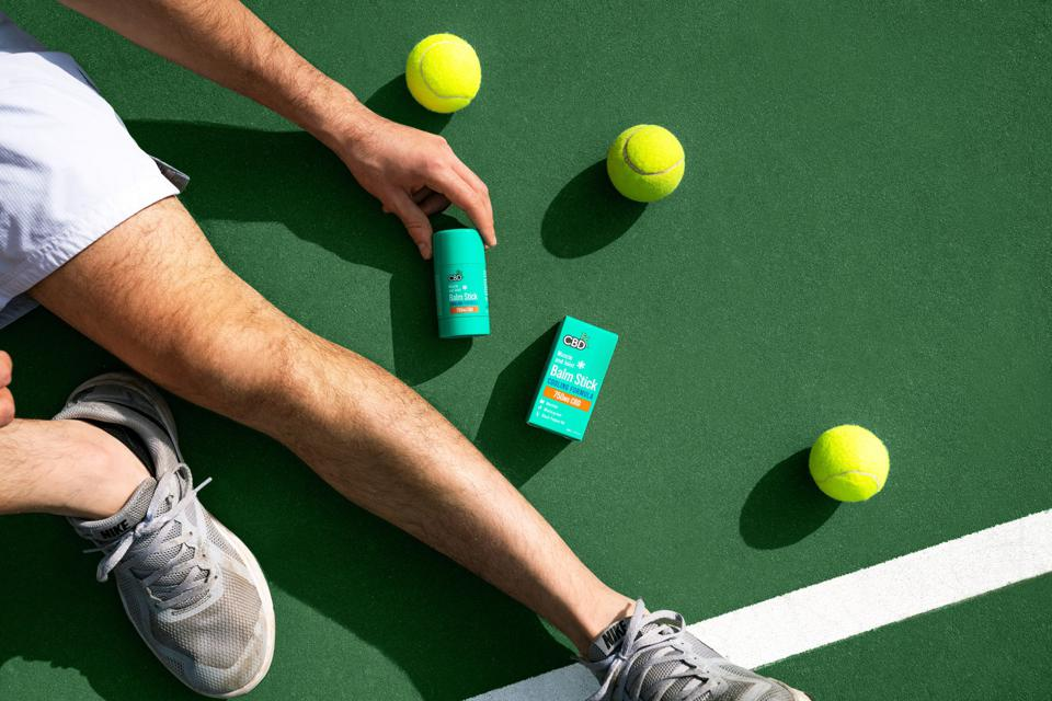 A man holds CBDFx's Muscle and Joint Balm sticks on a tennis court.