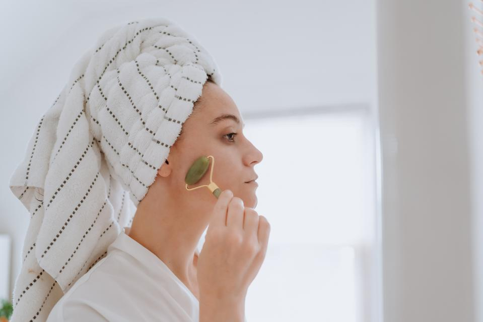 Woman using jade roller on her face at home.