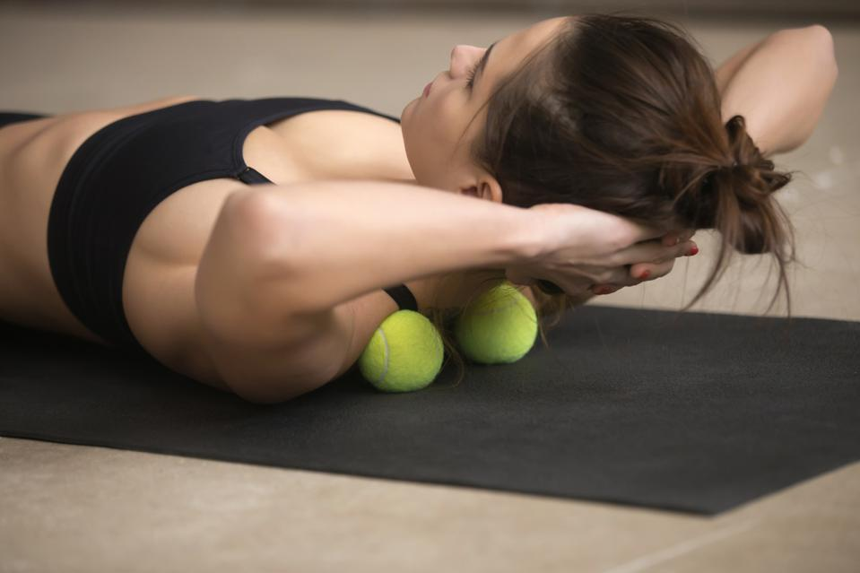 Young sporty woman practicing self-massage technique with tennis balls.