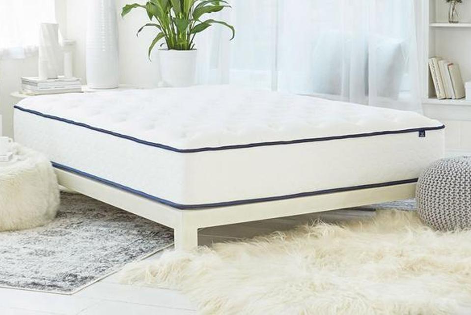 WinkBeds mattress set up next to a fuzzy rug.