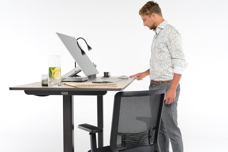 A man adjusts the Yaasa Adjustable Desk.