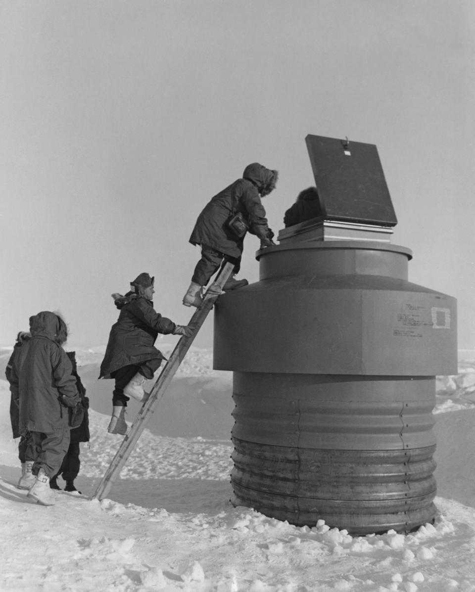 U.S. military personnel entering a pipe that accessed Camp Century, in 1959.