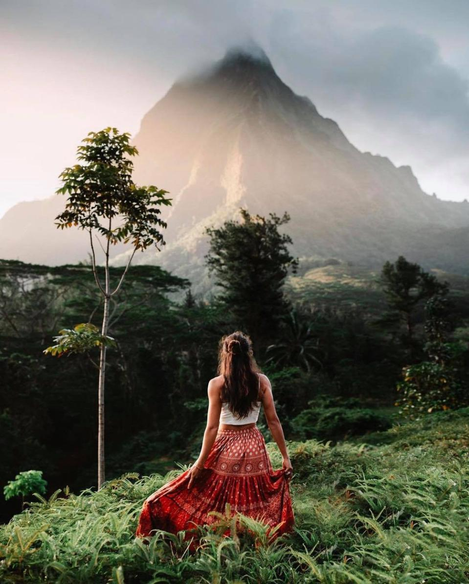 Travel influencer Chelsea Kauai in front of a remote mountain.