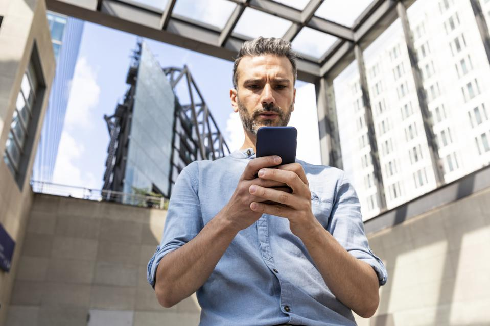 Serious businessman looking at the smartphone in the city, Berlin, Germany