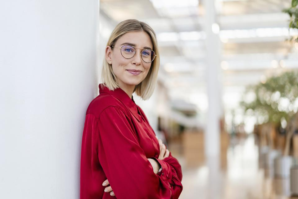 Portrait of a confident young businesswoman leaning against a column