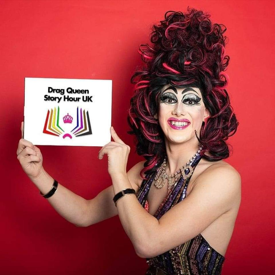 Image of Aida H Dee from Drag Queen Story Hour, holding their logo, smiling