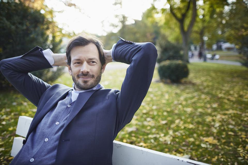 Smiling businessman contemplating on bench in park