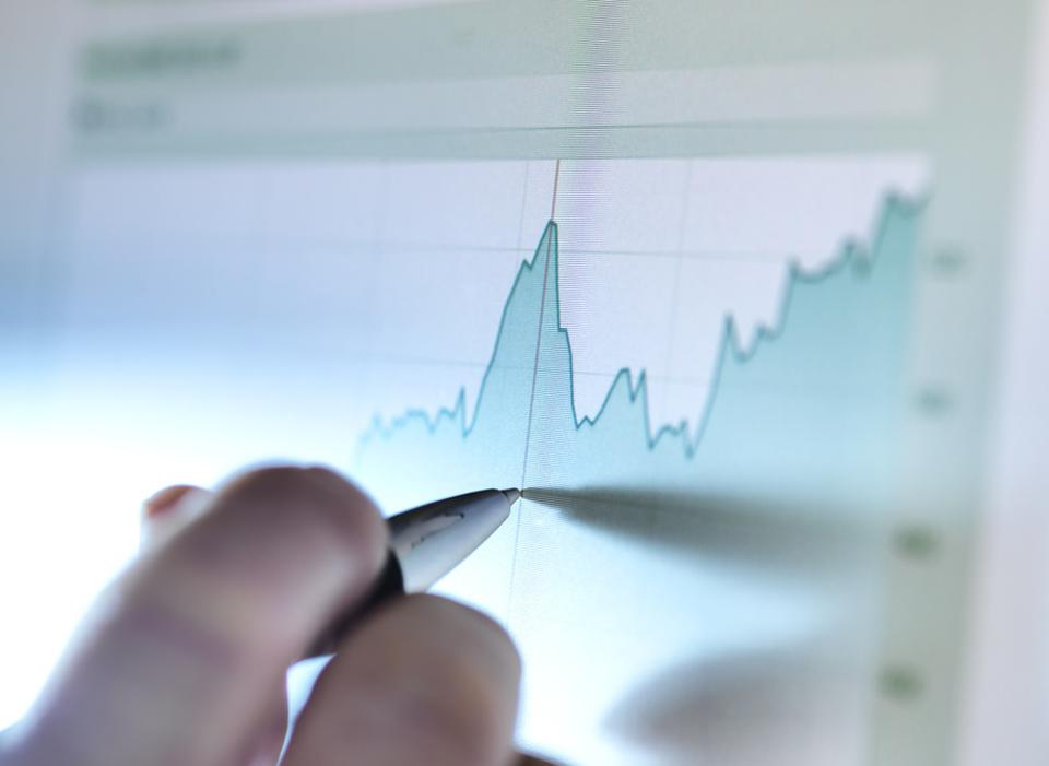 Hand of a stock broker analyzing line graph on computer screen