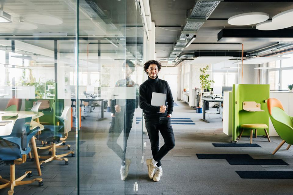 Portrait Of Office Worker Leaning On Glass Pane