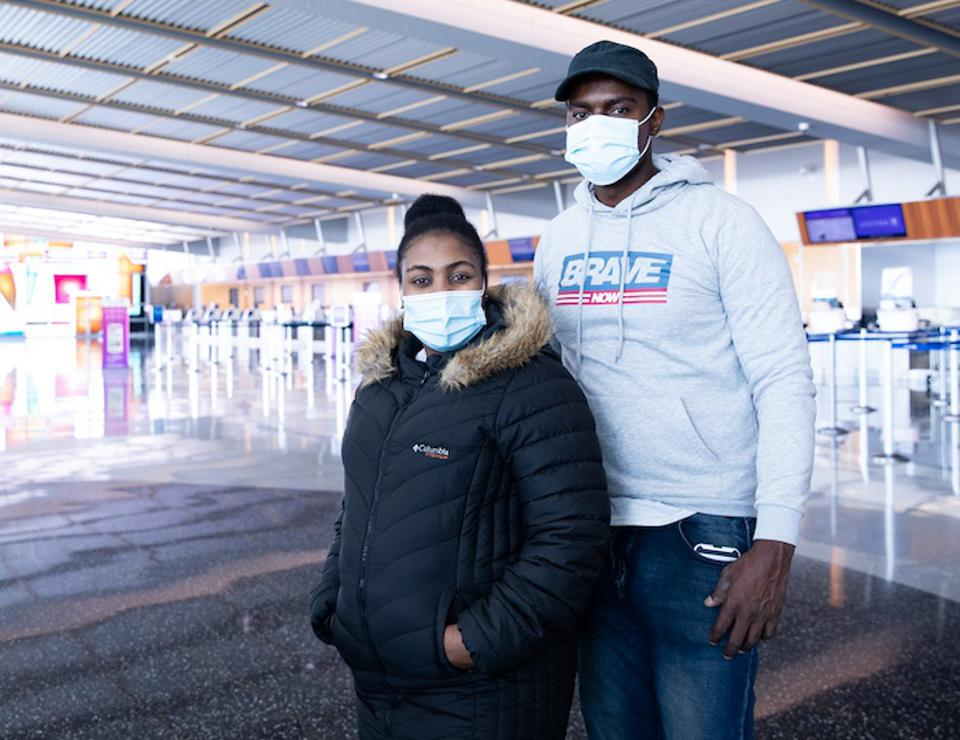 A man and a woman wearing masks to prevent the spread of COVID-19 stand in an empty waiting room.