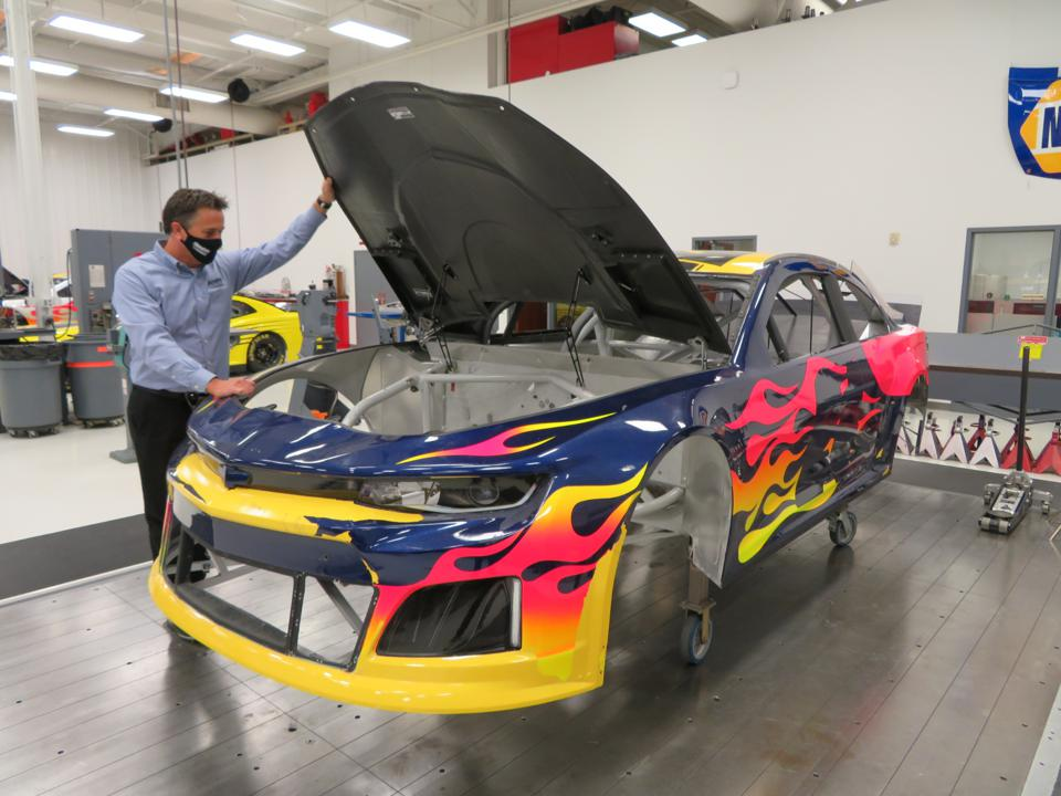 Dale Ledbetter, Vice President of Hendrick Performance Group, examines a retired William Byron car being prepared for Track Attack.